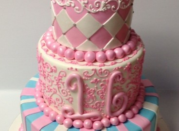 Pink With Mask Three Tier Fondant Sweet 16 With Mask Topper.Each Tier With Different Pattern.Stripes On The Lower Base Tier,Followed By Hand Scroll Work And A Whimsical Styled 16.Diamond Pattern Topper Cake With A Mask You May Also Like