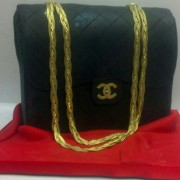 Black And Gold Gucci Pocketbook Set On A Satin Red Fondant Cloth Display.Whether it's their favorite purse designer, or their favorite handbag in general this unique cake will definitely catch their eye.