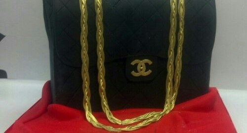 Black And Gold Gucci Pocketbook Set On A Satin Red Fondant Cloth Display.Whether it's their favorite purse designer, or their favorite handbag in general this unique cakewill definitely catch their eye.