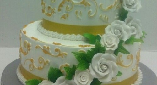 Two Tier Butter Cream With Hand Painted Gold Scroll High Lights With Elegant ,White Cascading Roses. The Top And Bottom Tiers Cumulate in Beautiful White Bouquets